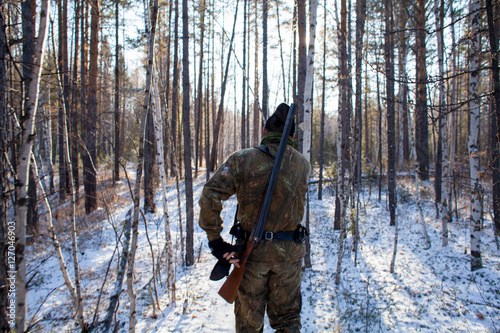Foto op Canvas Jacht a hunter in the winter woods with a gun in camouflage clothing.