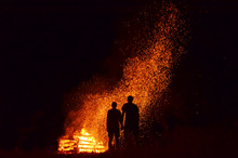 Young People In Love Standing Together In Front Of Big Fire And Looking At Beautiful Sparks In Air.