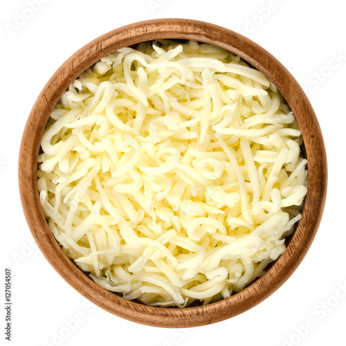 Shredded mozzarella pizza cheese in wooden bowl over white. Cheddar like semi hard Italian cheese made from milk, covered with corn starch. Isolated macro food photo close up from above.