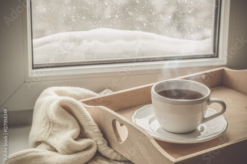 Staande foto Thee Tea on tray and sweater in from of snowing winter
