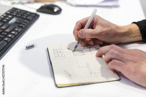 The Netherlands, Utrecht. Inside the factory of a Dutch design furniture brand.  Designer sketching in his notebook.