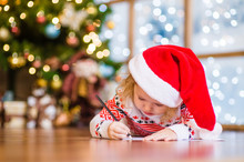 Little Girl In Red Christmas Hat Writes Letter To Santa Claus