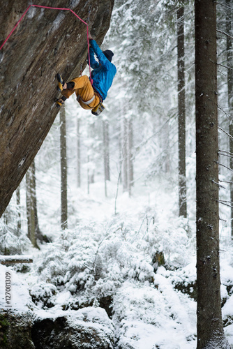 Poster Wintersporten Extreme winter sport. Young man climbing in beautiful Karelian forest.