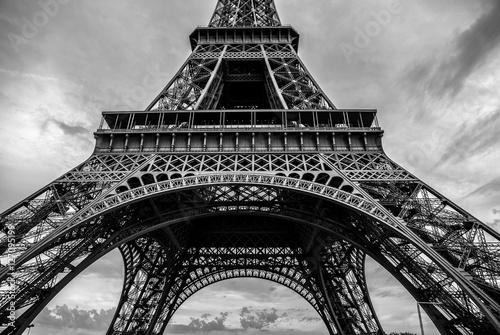 Papiers peints Paris Black-white photo of close-up element part of Eiffel tower in Paris against dramatic twilight sky at evening summer time.