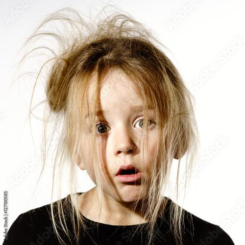 Photo Disheveled preschooler girl with stupid face