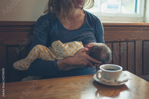Fotomural  Woman breastfeeding baby in cafe