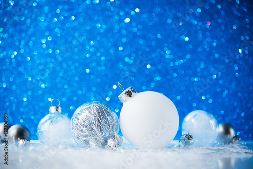 Silver And White Christmas Ornaments On Blue Glitter Bokeh