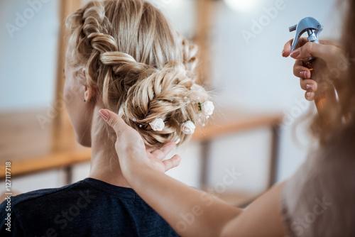 Foto auf AluDibond Friseur Female hairdresser making hairstyle to blonde girl in beauty salon.