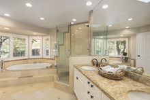 Luxury Bathroom Interior In Marble With Glass Shower And Oval Bath Tub And Round Shaped Double Sink.