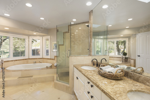 Foto  Luxury bathroom interior in marble with glass shower and oval bath tub and round shaped double sink
