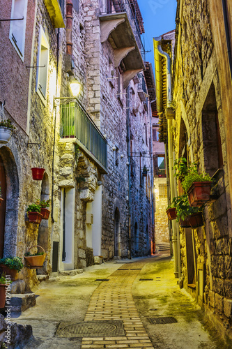 Foto op Plexiglas Trappen Narrow street with flowers in the old town Peille in France. Nig