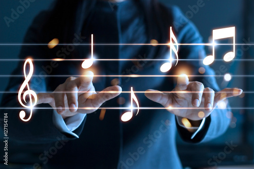 Fotografia Woman hands playing music notes on dark background, music concept