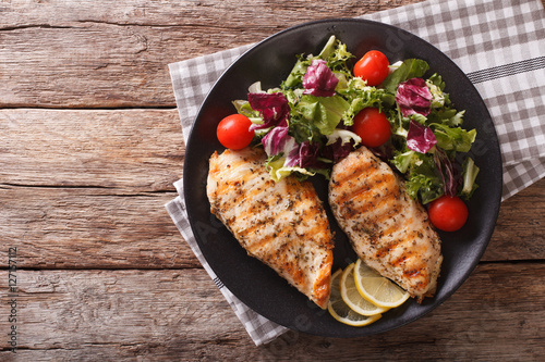 Fotografía  roasted Chicken breast with mix salad of chicory, tomatoes and lettuce close-up