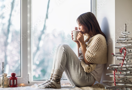 Foto auf AluDibond Kaffee Young beautiful woman drinking hot coffee sitting on window sill