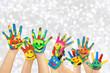 Leinwandbild Motiv angemalte Kinderhände vor weihnachtlichem Hintergrund