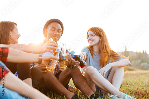 Fotografía  Group of happy young friends drinking beer and soda outdoors
