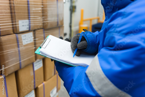 Valokuva  Closeup shooting hand of worker with clipboard checking goods in freezing room or warehouse