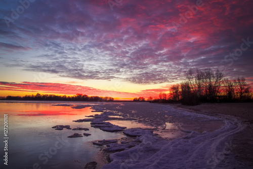 Beautiful colorful winter landscape with frozen lake and sunset