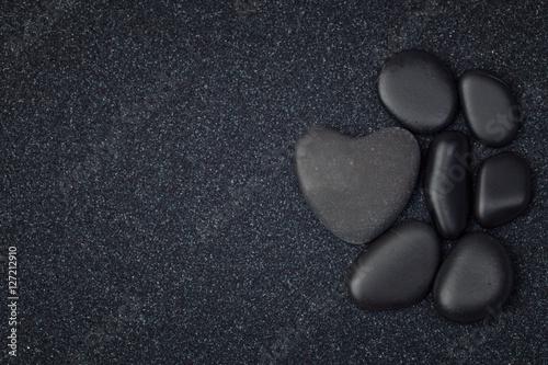 Tuinposter Stenen in het Zand Black stones with black zen heart shaped rock on grain sand