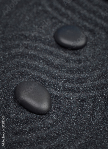 Tuinposter Stenen in het Zand Black stones aligned in a diagonal line with waves in a the background
