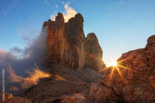 Fotografie, Tablou  Fog, lit by the sun at sunset among the rocks the Cime di Lavaredo the Tre, Dolo