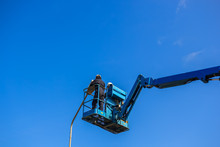 Electrical Technician Repairing Street Light By Boom Lift In Industrial