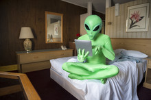 Green Alien Sitting Using Futuristic Tablet Computer On The Bed In An Old-fashioned Room