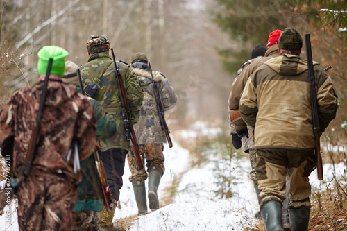 Tablou Canvas Group of hunters walking in the forest. Winter hunting