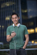 Asian man using phone in city at night.