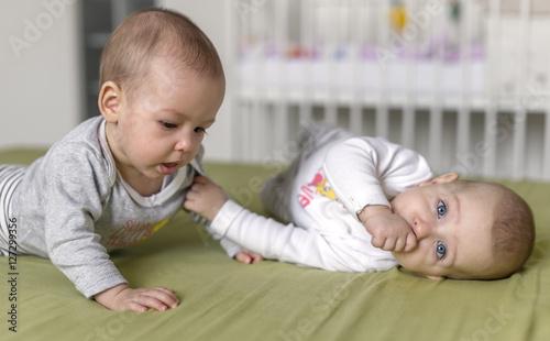 Valokuvatapetti Cheerful twins on the bed