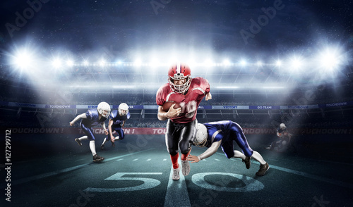 American football players in action on stadium with ball Canvas Print