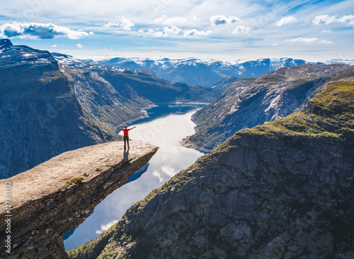 Young woman relaxon Trolltunga. Happy girl enjoy beautiful lake and good weather in Norway.