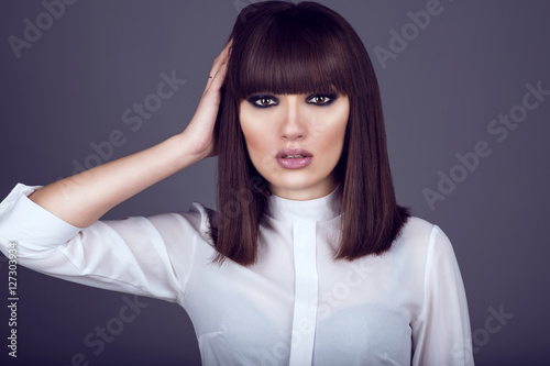 Fotografie, Obraz  Portrait of gorgeous young dark-haired woman with provocative make up and expressive eyes looking straight and touching hair with her hand