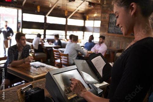 Tuinposter Restaurant Young woman preparing bill at restaurant using touch screen