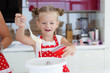 Little housewife blonde girl is 5 years old, his hair neatly gathered, dressed in a white vest and a red apron with white polka dots, prepares the dough for baking cakes in colorful forms