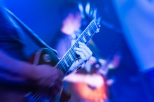 Musician Playing Electric Guitar Under Blue Stage Stage Lighting