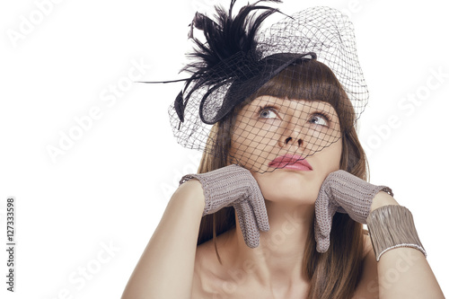Pensive sad pretty young lady with fringe haircut wearing gloves and black  vintage feather light hat with net veil. Retro styled woman daydreaming  with ... 809bd11063b4
