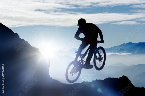 Photo springender Mountainbiker im Gebirge im Gegenlicht