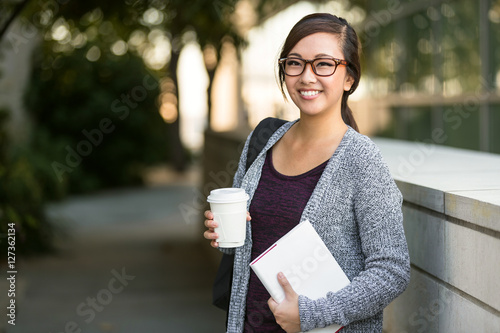 Photo  Asian female financial business student earning a degree as an accountant holdin