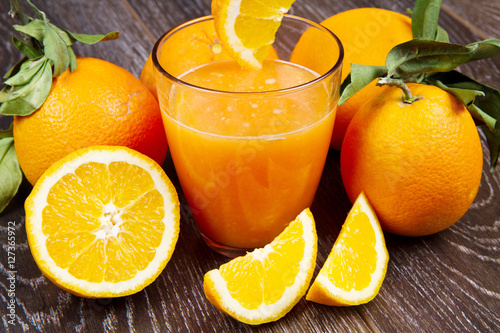 glass of fresh orange juice and oranges on wooden background