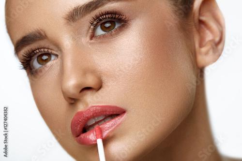 Fotografía  Beautiful Woman Doing Makeup Using Lip Gloss On Lips. Cosmetics