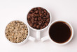 Three white cups with different stages of coffee: green and roasted beans and ready drink