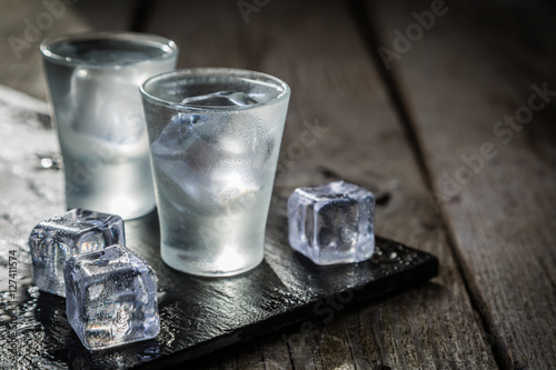 Vodka in shot glasses on rustic wood background Fototapeta