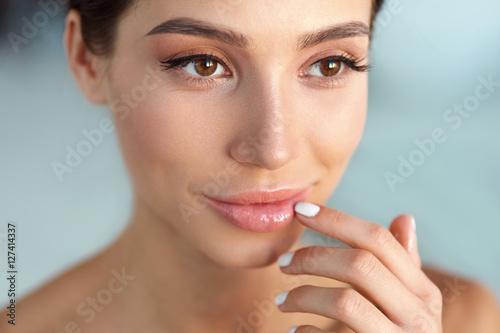 Stampa su Tela Beauty Face. Beautiful Woman Touching Lips With Lip Balm On