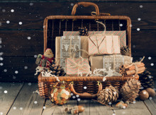 Gift Box In A Wicker Basket With Tree Branches And Cones