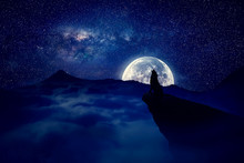 Lonely Wolf Silhouette Howls On A Cliff Over Full Moon Night Background. Mysterious Scene Werewolf Halloween Scary View.