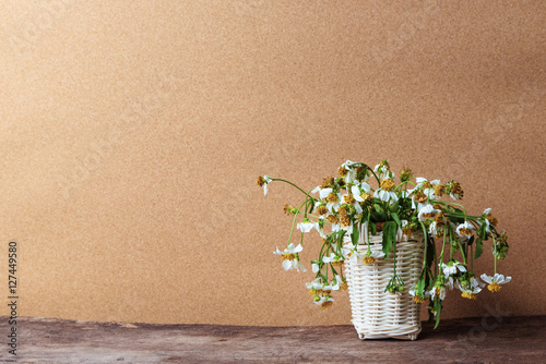 Valokuva  white flowers in basket on wooden table with brown paper background, vintage tone