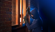 Burglar Using Crowbar To Break...