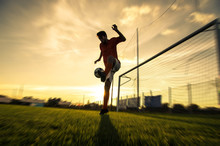 Silhouette Of A  Soccer Player On A Football Field At Sunset.