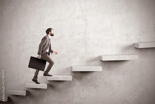 Obraz na płótnie Side view of businessman climbing a concrete stair